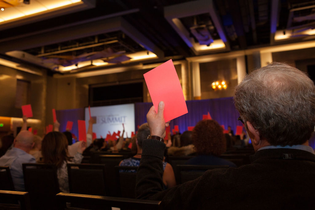 Members vote on a motion at the annual business meeting. Red cards are raised by the voters.