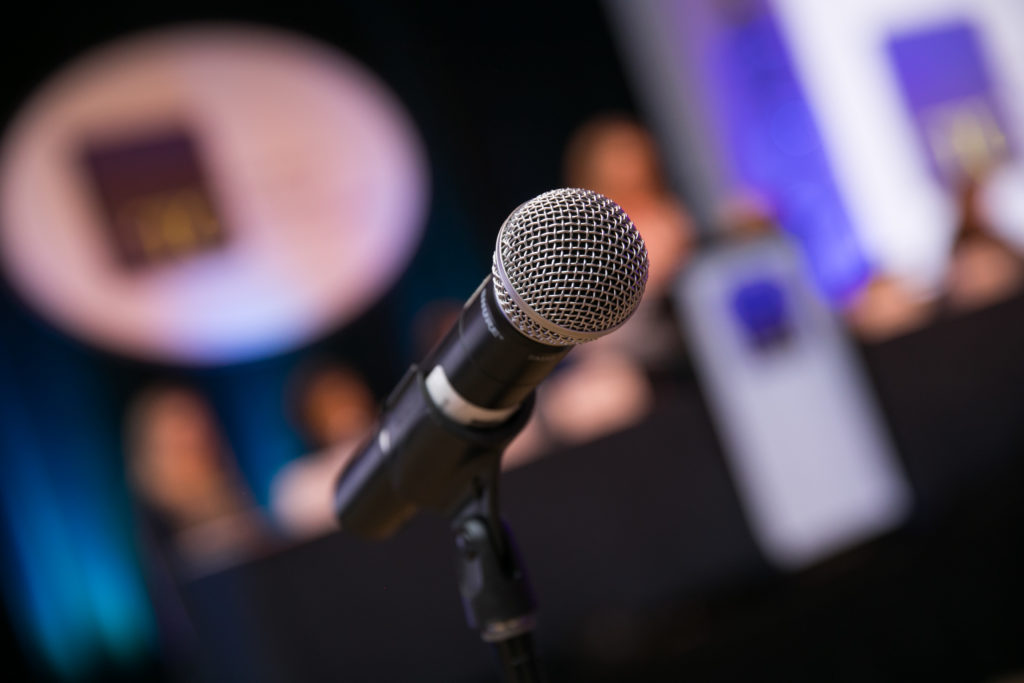 A microphone appears in the foreground, while a blurred stage is in the backgrouncd.