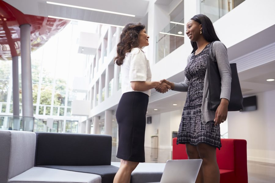 two-businesswomen-shaking-hands-in-lobby-of-modern-office-900×600